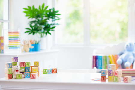 Child learning letters and numbers. Kid with colorful wooden abc blocks. Little boy spelling words with educational block toys. Kids doing school homework at white desk. Bedroom for preschool children Imagens