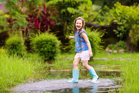 Kid playing out in the rain. Children with umbrella and rain boots play outdoors in heavy rain. Little boy jumping in muddy puddle. Kids fun by rainy autumn weather. Child running in tropical storm. 版權商用圖片