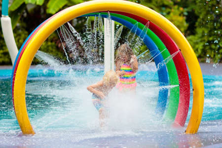 Kids play in aqua park. Children at water playground of tropical amusement park. Little girl and boy at swimming pool. Child playing at water slide on summer vacation in Asia. Swim wear for young kid. Stock Photo