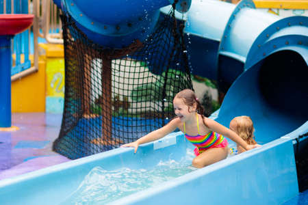 Kids play in aqua park. Children at water playground of tropical amusement park. Little girl and boy at swimming pool. Child playing at water slide on summer vacation in Asia. Swim wear for young kid. Stockfoto