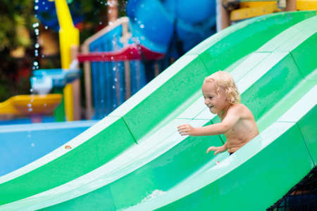 Kids play in aqua park. Children at water playground of tropical amusement park. Little boy at swimming pool. Child playing at water slide on summer vacation in Asia. Swim wear for young kid.