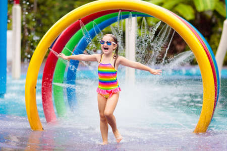 Kids play in aqua park. Children at water playground of tropical amusement park. Little girl at swimming pool. Child playing at water slide on summer vacation in Asia. Swim wear for young kid. Stock Photo - 123773394
