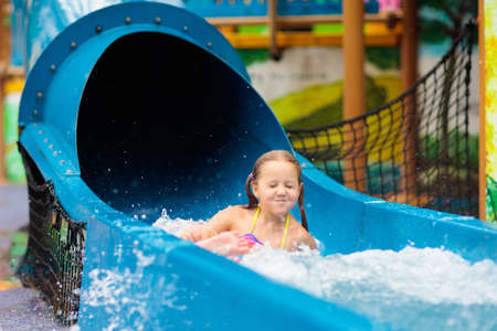 Kids play in aqua park. Children at water playground of tropical amusement park. Little girl at swimming pool. Child playing at water slide on summer vacation in Asia. Swim wear for young kid. Stock Photo - 123773648
