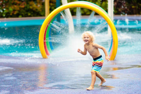 Kids play in aqua park. Children at water playground of tropical amusement park. Little boy at swimming pool. Child playing at water slide on summer vacation in Asia. Swim wear for young kid. Stock Photo - 123773662