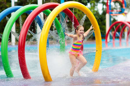 Kids play in aqua park. Children at water playground of tropical amusement park. Little girl at swimming pool. Child playing at water slide on summer vacation in Asia. Swim wear for young kid. Stock Photo - 123773665