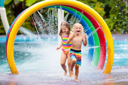 Kids play in aqua park. Children at water playground of tropical amusement park. Little girl and boy at swimming pool. Child playing at water slide on summer vacation in Asia. Swim wear for young kid. Stock Photo - 123773667