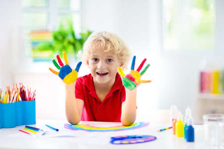 Kids paint. Child painting in white sunny study room. Little boy drawing rainbow. School kid doing art homework. Arts and crafts for kids. Paint on children hands. Creative little artist at work. Stock Photo