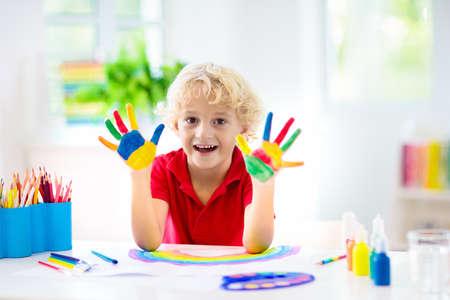 Kinder malen. Kindermalerei im weißen sonnigen Arbeitszimmer. Kleiner Junge, der Regenbogen zeichnet. Schulkind, das Kunsthausaufgaben macht. Kunsthandwerk für Kinder. Kinderhände malen. Kreativer kleiner Künstler bei der Arbeit. Standard-Bild