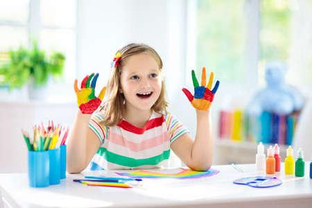 Kinder malen. Kindermalerei im weißen sonnigen Arbeitszimmer. Kleines Mädchen, das Regenbogen zeichnet. Schulkind, das Kunsthausaufgaben macht. Kunsthandwerk für Kinder. Kinderhände malen. Kreativer kleiner Künstler bei der Arbeit.