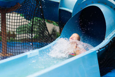 Kids play in aqua park. Children at water playground of tropical amusement park. Little girl at swimming pool. Child playing at water slide on summer vacation in Asia. Swim wear for young kid. Stock Photo - 123775524