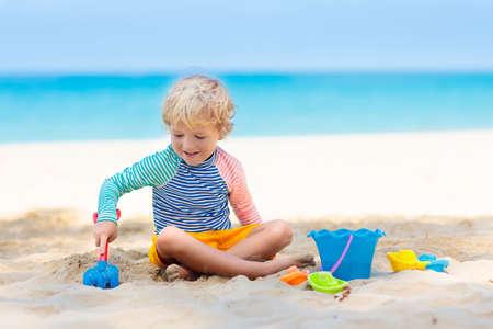 Kinder spielen am tropischen Strand. Kinder spielen im Sommer Familienurlaub auf See. Sand- und Wasserspielzeug, Sonnenschutz für Kleinkinder. Kleiner Junge, der Sand gräbt, Burg am Meeresufer baut.