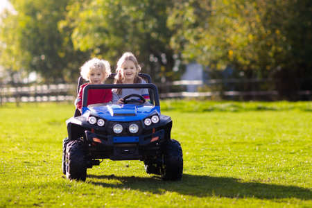 Kids driving electric toy car in summer park. Outdoor toys. Children in battery power vehicle. Little boy and girl riding toy truck in the garden. Family playing in the backyard. Stock Photo - 123776181