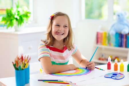 Kinderen schilderen. Kind schilderen in witte zonnige studeerkamer. Meisje tekening regenboog. Schooljongen die kunsthuiswerk doet. Kunst en handwerk voor kinderen. Verf op kinderhanden. Creatieve kleine kunstenaar aan het werk. Stockfoto