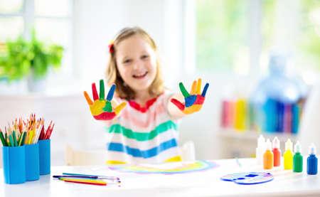 Kinder malen. Kindermalerei im weißen sonnigen Arbeitszimmer. Kleines Mädchen, das Regenbogen zeichnet. Schulkind, das Kunsthausaufgaben macht. Kunsthandwerk für Kinder. Kinderhände malen. Kreativer kleiner Künstler bei der Arbeit. Standard-Bild