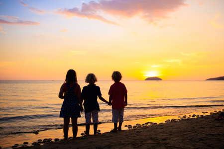 Kind, das am Ozeanstrand spielt. Kind springt bei Sonnenuntergang in die Wellen. Urlaub am Meer für Familie mit Kindern. Sommerinsel im Sommerurlaub