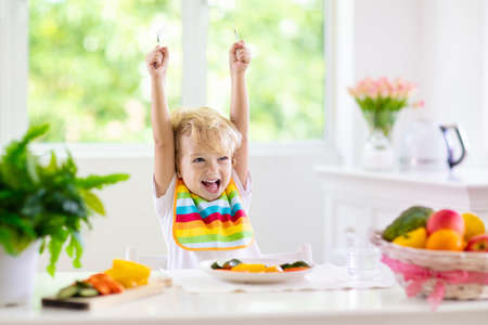 Child eating vegetables sitting in white high chair. Solid food for baby. Little boy eating healthy vegetable lunch of steam cooked carrots. Nutrition for toddler and preschooler. Kids eat fruit. 版權商用圖片 - 123776203