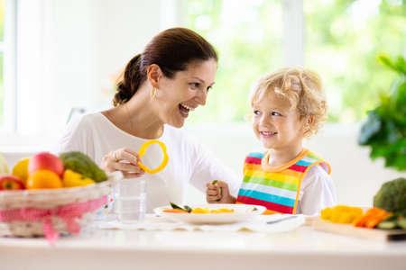 Moeder die kindgroenten voedt. Moeder voedt kind in witte keuken met raam. Babyjongen zittend in een kinderstoel die een gezonde lunch eet van gestoomde wortel en broccoli. Voeding, vegetarisch dieet voor peuters Stockfoto