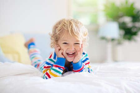 Kind, das im Bett im weißen sonnigen Schlafzimmer mit Fenster spielt Kinderzimmer und Innenarchitektur. Baby zu Hause. Bettwäsche und Textilien für Kinderzimmer. Kind mit Spielzeug und Buch. Nickerchen und Schlafenszeit.