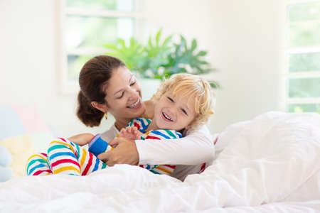 Mother and child playing in bed on sunny morning. Mom and baby relaxing in white bedroom at home. Young woman tickling little boy. Family happiness and love. Parent and kid after sleep. Kids room.