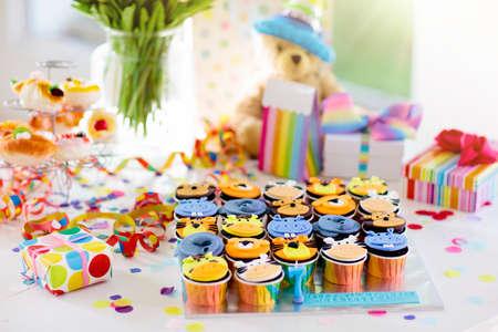 Cupcakes para celebración de cumpleaños de niños. Fiesta infantil temática de animales de la selva. Habitación decorada para cumpleaños de niño o niña. Ajuste de la tabla con regalos, cajas de regalo, confeti y dulces. Pastelería para niño