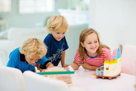 Los niños juegan juegos de mesa. Grupo de niños en edad preescolar que juegan juegos educativos sentados en un escritorio blanco en la sala de clase soleada. Niño y niña con juguetes nuevos. Niño en casa o guardería. Juegos para niños de la escuela.