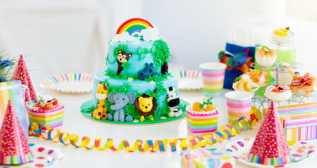 Cake for kids birthday celebration. Jungle animals theme children party. Decorated room for boy or girl kid birthday. Table setting with presents, gift boxes, confetti and sweets. Pastry for child