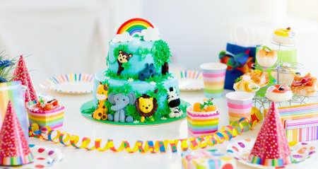 Kuchen für Kindergeburtstagsfeier. Dschungeltiere Thema Kinderparty. Dekorierter Raum für Jungen- oder Mädchengeburtstag. Tischdekoration mit Geschenken, Geschenkboxen, Konfetti und Süßigkeiten. Gebäck für Kinder