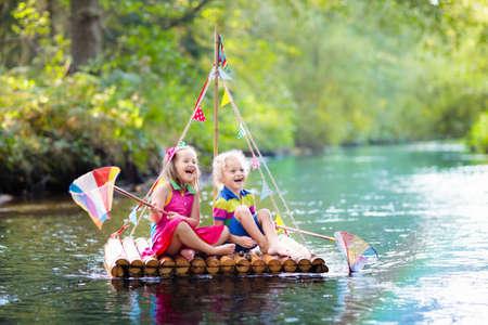 Dwoje dzieci na drewnianej tratwie łowi ryby kolorową siatką w rzece i bawi się wodą w upalny letni dzień. Zabawa na świeżym powietrzu i przygoda dla dzieci. Chłopiec i dziewczynka w łodzi zabawki. Gra z rolą marynarza. Zdjęcie Seryjne
