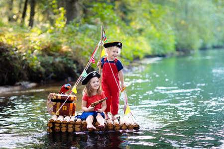 Kinder in Piratenkostümen und Hüten mit Schatztruhe, Fernglas und Schwertern, die an heißen Sommertagen auf einem Holzfloß spielen, das in einem Fluss segelt. Piraten-Rollenspiel für Kinder. Wasserspaß für die Familie.