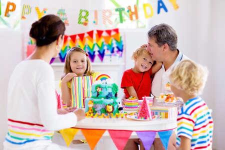 Fiesta de cumpleaños para niños. Niño soplando velas en la torta y abriendo regalos en la celebración del tema de la selva. Familia celebrando en casa. Madre, padre, niño y niña abren regalos, comen pasteles. Dulces para niños