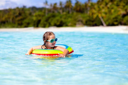 Child with inflatable ring on beautiful beach. Little girl swimming in exotic sea. Ocean vacation with kid. Children play on summer beach. Water fun. Kids swim. Family holiday on tropical island. 写真素材