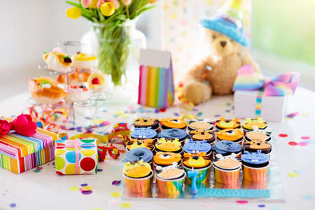 Cupcakes for kids birthday celebration. Jungle animals theme children party. Decorated room for boy or girl kid birthday. Table setting with presents, gift boxes, confetti and sweets. Pastry for child
