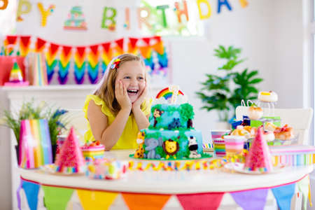 Kids birthday party. Child blowing candles on cake and opening presents on jungle theme celebration. Sweets and cakes for children event. Kid celebrating birthday. Table setting with gifts and pastry. Stock Photo