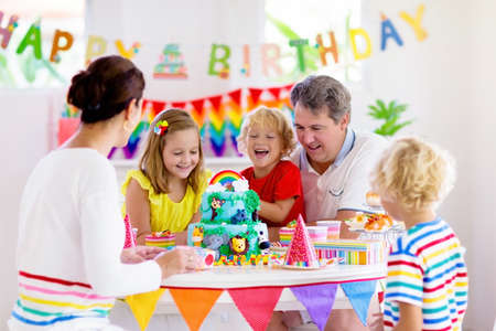 Kids birthday party. Child blowing candles on cake and opening presents on jungle theme celebration. Family celebrating at home. Mother, father, boy and girl open gifts, eat cakes. Sweets for children Stock Photo