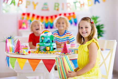 Kids birthday party. Child blowing candles on cake and opening presents on jungle theme celebration. Cakes dessert for children event. Boy and girl celebrate birthday. Gifts and sweets for kid.