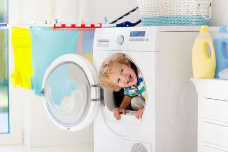 Child in a laundry room with washing machine or tumble dryer. Kid helping with family chores. Modern household devices and washing detergent in white sunny home. Clean washed clothes on drying rack.