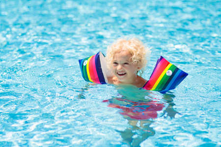 Child in swimming pool wearing colorful inflatable armbands. Kids learn to swim with float aid. Floaties for baby and toddler. Healthy summer outdoor sport activity for children. Water and beach fun. Stockfoto