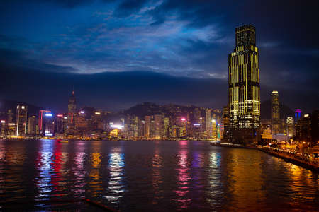 Hong Kong harbor at night. City skyline at sunset. Skyscraper district with colorful lights in the evening.