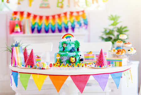 Kids birthday party. Child blowing candles on cake and opening presents on jungle theme celebration. Cakes dessert for children event. Boy and girl celebrate birthday. Gifts and sweets for kid. Stock Photo