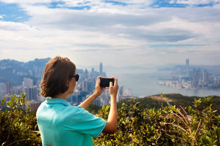 Young man hiking in Hong Kong mountains taking photo with smart phone camera of landscape with hills, sea and city skyscrapers in Hong Kong, China. Outdoor activity in the nature.