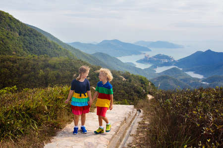 Family with kids hiking in Hong Kong mountains. Beautiful landscape with hills, sea and city skyscrapers in Hong Kong, China. Outdoor activity in the nature for parents and children.