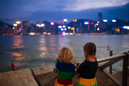 Kids watch Hong Kong harbor skyline at night. Travel with young children. Beautiful view of skyscraper and sea harbor at sunset.