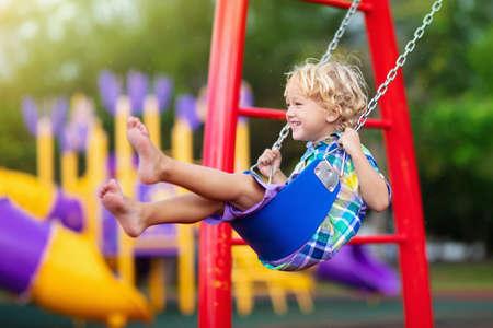 Kind, das im Regen auf Spielplatz im Freien spielt. Kinder spielen auf dem Schul- oder Kindergartenhof. Aktives Kind auf bunter Schaukel. Gesunde Sommeraktivität für Kinder bei Regenwetter. Kleiner Junge schwingt. Standard-Bild