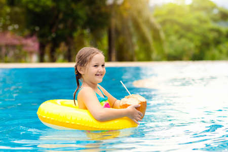 Child with coconut drink in outdoor swimming pool. Kids swim in tropical resort. Healthy exotic fruit refreshment for children. Travel with young kid. Beach and water fun. Summer family vacation.