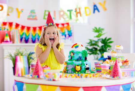 Fiesta de cumpleaños para niños. Niño soplando velas en la torta y abriendo regalos en la celebración del tema de la selva. Evento de dulces y tartas para niños. Niño celebrando un cumpleaños. Mesa con regalos y pastelería.