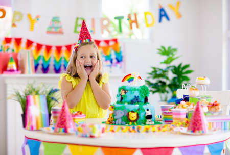 Kids birthday party. Child blowing candles on cake and opening presents on jungle theme celebration. Sweets and cakes for children event. Kid celebrating birthday. Table setting with gifts and pastry.