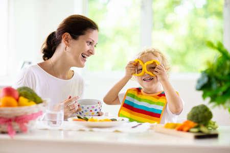 Mère nourrissant les légumes de l'enfant. Maman nourrit un enfant dans une cuisine blanche avec fenêtre. Petit garçon assis dans une chaise haute mangeant un déjeuner sain de carottes et de brocoli cuits à la vapeur. Nutrition, régime végétarien pour tout-petit