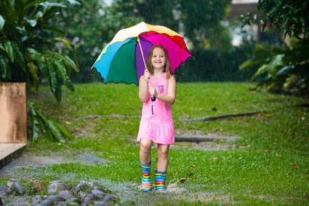 Kind, das draußen im Regen spielt. Kinder mit Regenschirm und Regenstiefeln spielen bei starkem Regen im Freien. Kleines Mädchen, das in schlammige Pfütze springt. Kinderspaß bei regnerischem Herbstwetter. Kind läuft im tropischen Sturm.