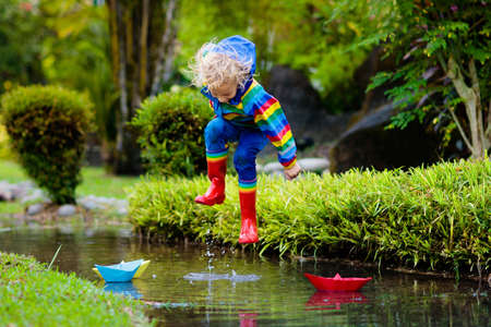 Child playing with paper boat in puddle. Kids play outdoor by autumn rain. Fall rainy weather outdoors activity for young children. Kid jumping in muddy puddles. Waterproof jacket and boots for baby.