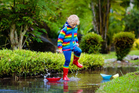 Child playing with paper boat in puddle. Kids play outdoor by autumn rain. Fall rainy weather outdoors activity for young children. Kid jumping in muddy puddles. Waterproof jacket and boots for baby. Banque d'images - 126112486